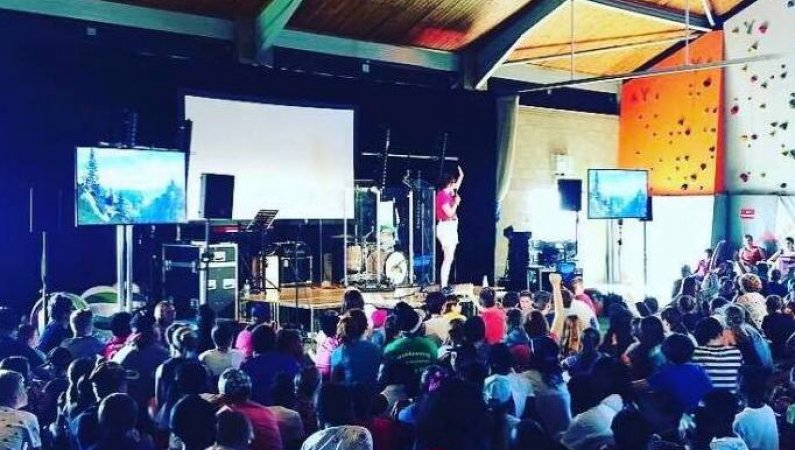 Emily Wright standing on a stage at the 11-14s venue at the 2019 Spree Central weekend Camp, with hundreds of young people listening